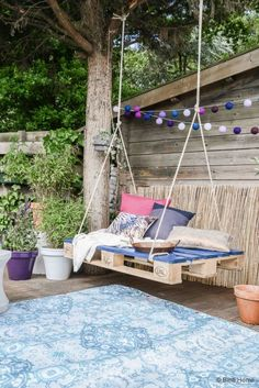 File this under the easiest porch swing ever: Just loop a rope underneath both sides of a pallet and hang it from a sturdy tree. Pillows are a must to transform this seat into a cozy hideout. Click through more cool DIY outdoor swings.