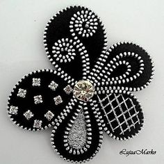 A brooch with black and silver colors in the shape of the flower. The elegant brooch is handmade sew, decorated with zipper, crystal, strass, beads and threads. Components in silver color. The back is padded with felt, with a brooch bridle to attach to the dress. Size: approx. 7.7 x