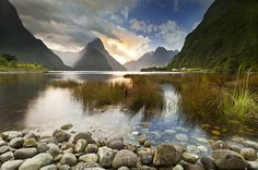 Milford Sound, Fiordland New Zealand. The star of this image is the dramatic light playing out in the clouds over the eye- catching form of Mitre Peak – the foreground & mid ground elements are critical supporting parts of the whole composition but don't hog the lime-light.