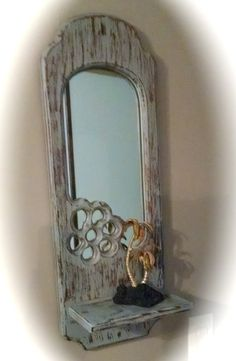 """1970s hand made wall mirror shelf. This is a vintage mirror in a wood frame with a shelf at the bottom. These were popular in the 1970s. This is approximately 11"""" wide, 6"""" deep shelf at bottom and 30"""" long.  The mirror is anchored with 4 clips and there is a sturdy piece on top to hang it by. The lower right hand corner has a flower carved out of it...flowers were the rage then!"""