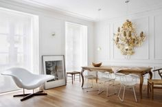 Love the all the white.  The raditional wood table with the modern chairs.  Hate the gold sculpture on the wall.  Would do something else for texture.