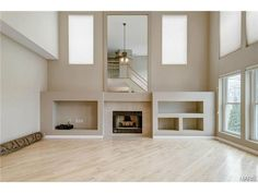 Modern fireplace with large custom mirror and built-in storage. 715 Bellerive Manor Drive, St Louis, MO 63141