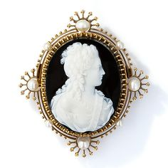 A classic Victorian beauty with long curly tresses is masterfully hand carved in glorious black and white in this superb and sizable hard stone cameo presented in consummate Victorian style. The lovely open frame shimmers with eight natural pearls of varying sizes and is adorned all around with delicate bead work punctuated by crown motifs. This exemplary antique cameo measures 2 and 5/16 inches and is equipped with a flip-up necklace loop.