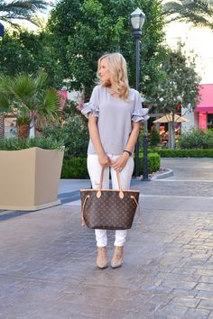 grey ruffle sleeve blouse with white jeans and louis vuitton never full