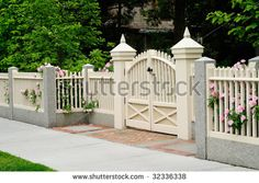 Elegant gate and fence of residential house. Wood, granite, brick; rose bushes coming out through picket posts - stock photo