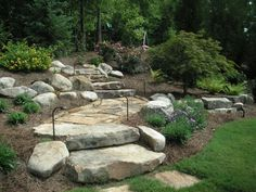 A boulder wall landscape steps stone edging on a short landing of flagstone walkway trees shrubs and a large block retaining wall Landscaping lighting also lines the walk. Landscape Steps, Landscape Borders, House Landscape, Landscape Plans, Landscape Design, Garden Design, Tiered Landscape, Boulder Landscape, Landscape Bricks