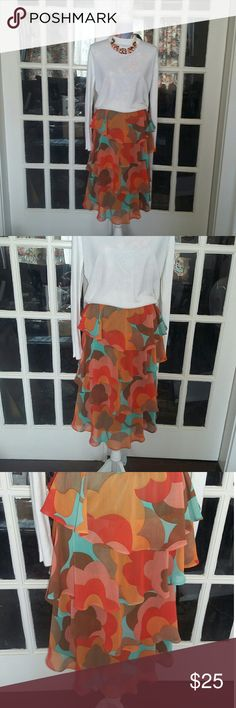 Judith March Floral Ruffle Tiered Skirt EUC Really nice skirt by Judith March size medium. It is 100% polyester and does have a liner. The skirt is done w/ ruffled tiers and in beautiful vibrant colors of turquoise Orange and brown. Measurements are in the photo gallery. Please let me know if you have any questions. The skirt has no defects. Judith March Skirts Midi
