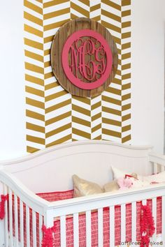 Gold herringbone accent wall in the nursery - we love it with the layered monogram on top!