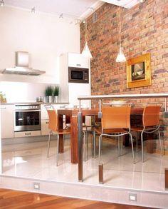 Kuchnia i kąt jadalny znajdują się na niskim podeście, w który wmontowano światełka. W kuchni dominuje stal. Żeby nieco złagodzić efekt