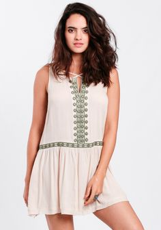 Beige-toned, tunic-style dress designed with a drop waist silhouette and sage green embroidery at the waistline and down the front, accented with mirrored details.