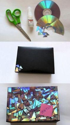 Materiales: • Caja. • Pegamento. • CD. • Tijera. • Pintura negra.  Procedimiento: 1. Pinta la caja de cartón con dos capas de pintura de color negro y cuando se haya secado comenzaremos a decorarlo. 2. Recorta varios trozos de CD y luego unta pegamento en la superficie de la caja para comenzar a pegarlos. 3. Acomoda los trozos de CD sobre la superficie de la caja y no debe quedar espacio entre ellos. 4. Deja que se seque el pegamento y ya podrás utilizarlo para lo que desees.