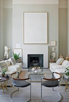 A contemporary style living room designed by Daniel Romauldez. A pair of contemporary chairs, the minimalist lines of the fireplace, and symmetry of floorplan. Featured in All the Pretty Houses of the Wall Street Journal.