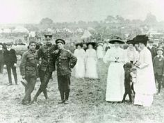 Camp at Hackwood Park, Basingstoke  Photographed early in the First World War, these elegantly dressed ladies in picture hats have come to visit the camp of the Ist Volunteer Battalion, Hampshire Regiment, at Hackwood Park.  The three soldiers to the left are clearly not overawed and have struck a relaxed pose for the camera.  HMCMS:DPAAMO26