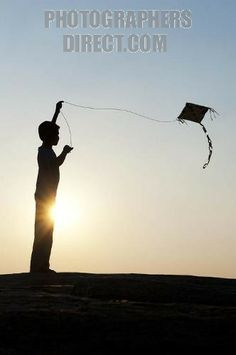 indian boy flying newspaper kite silhouette stock photo
