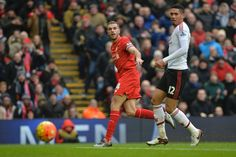 Liverpool's English midfielder Jordan Henderson and Manchester United's English defender Chris Smalling watch Henderson's shot go wide during the English Premier League football match between Liverpool and Manchester United at Anfield in Liverpool, northwest England, on January 17, 2016.