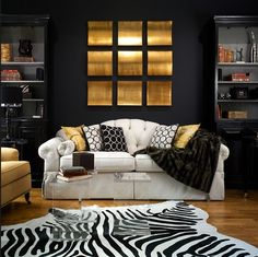 living rooms - Zebra Cowhide Rug black walls paint color black lamps acrylic lucite tables white gray tufted sofa gold brown accent chairs bookshelves black gold white living room
