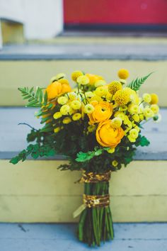 yellow ranunculus and craspedia bouquet // photo by Sarah Kathleen // http://ruffledblog.com/wizard-of-oz-wedding-inspiration