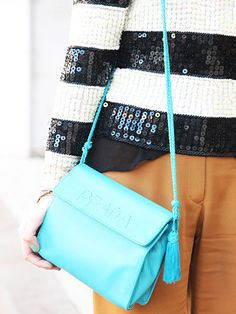 A bright blue bag adds just the right amount of color to a neutral outfit.