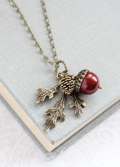 This is a beautiful rustic nature charm necklace! The woodland inspired charm cluster includes a 12mm cranberry red swarovski pearl acorn with rustic antiqued brass top, an antiqued gold pine cone with gorgeous details and a woodland branch of three leaves in antique gold brass. This