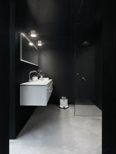 Vipp prefab Shelter black bathroom // The concrete floor adds great texture to this masculine space