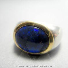 Ring mit einem Schwarzopal, Australien. Der tief saphirblaue Schwarzopal ist in 900/- Gold eingefasst. Er bringt ein sehr intensives blaues Farbspiel hervor.