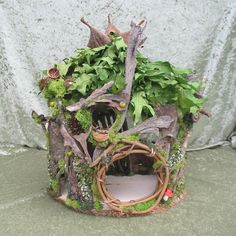 A cozy single level cottage for the little folk. Green oak leaves for a roof with dried pod accents. A rooftop nest for star gazing or guest bed. A