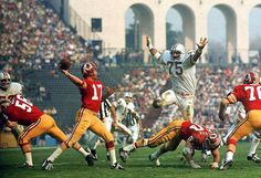 Dolphins defensive lineman Manny Fernandez (75) hurdles a Redskins offensive lineman in pursuit of quarterback Billy Kilmer (17). Fernandez would finish the game with 17 tackles as the Dolphins defeated the Redskins 14-7 to become the first and last team to finish an NFL season undefeated.