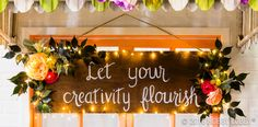 Bring a little whimsy to your garden party with a DIY sign! 1) Stain a spare piece of wood with your choice of color. 2) Sketch a saying onto the wood with pencil or chalk. 3) Paint your saying with white paint and let dry. 4) Add desired greenery and flowers onto the sign. 4) Add LED string lights with glue dots and hang!