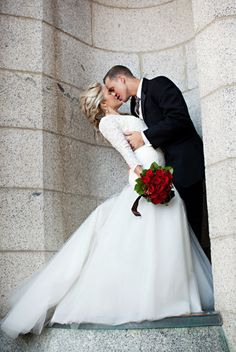 Love this shot of bride and groom, the red roses against the white dress are beautiful! #winterwedding #bride #groom #weddingfashion | http://www.mybigdaycompany.com/weddings.html
