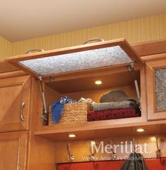 Wall Top Hinge Cabinet - Masterpiece® Accessories - Merillat® cabinetry. A glass insert adds a decorative touch to this cabinet, which opens from the bottom for easy access to the top shelves.