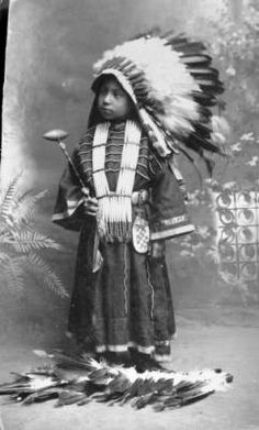 [between 1880 and 1910?] studio portrait of a Native American Dakota Sioux girl, Julie High Eagle, wearing a a headdress, dress with beadwork, and a hair pipe necklace; holding a fixed-stone-head club in front of a painted backdrop.