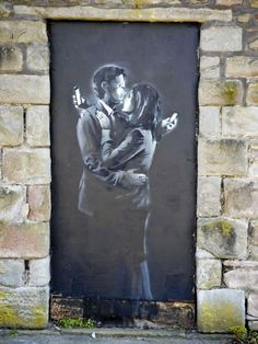 """""""Mobile Lovers"""" by Banksy in England. This piece was sold to a private collector for £403,000. Ch. 2 describes how art is valued and shows """"elements of hierarchy"""" when collected. This shows the evolution of street art from being vandalism to modern works of art and shows how taste for street art has transformed over the years. This work also uses monochromatic colors and contrast to send its message and create the illusion of light from the digital devices."""