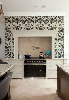 Black and White wallpaper makes a bold statement on the accent wall and Black Lacanche Range makes for a stunning kitchen