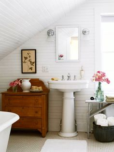 Under-the-eaves baths have the snug feeling often found in cottage-style rooms. White walls and flooring fit that style, too, and not only tie the room together, but also make the space feel larger. This bath's slanted design provides the ideal space for a wall-mounted mirror with a small chest of drawers beside it.