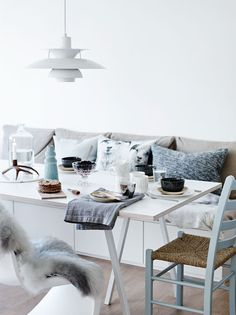 create a cushion bench with couch pillows and a white table. Comfy dining
