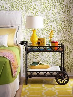 cart as a bedside table. top shelf {table lamp + flowers + radio + tissue box + books} bottom shelf {extra blankets + bedside reading book}