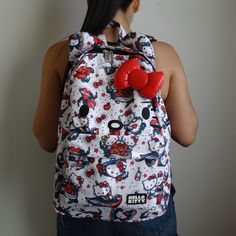 """Cute classic tattoo design by Loungefly x Hello Kitty. Comes with red 3D bow, interior laptop pocket and printed interior lining. Measurement: 17.5""""H x 11.5""""W x 5""""D - Printed nylon outer, polyester li"""
