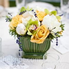 The low centerpieces included the same yellow roses, white peonies and green orchids as found in the bridesmaid bouquets.