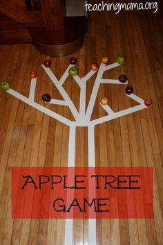 """This sounds like an amazing indoor gross motor activity! The children balance-walk on the tape, """"pick"""" one apple and """"climb"""" back down the tree to place in a basket below the trunk. Love it!"""