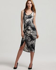 A high-contrast print of palm leaves in black and white, alluring ruching, and a dramatic side slit add up to a powerful presence in this Karen Kane dress.
