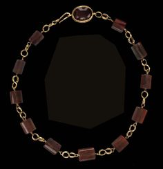 A ROMAN GOLD AND CARNELIAN NECKLACE   Circa 2nd Century A.D.   Composed of eleven carnelian beads, each threaded on a plain wire and looped at each end, and joined by double figure-8 loop-in-loop chain, one end terminating in a hook, the other joined to an oval box-shaped bezel set with a cabochon carnelian, the bezel's outer edge fringed with beaded wire