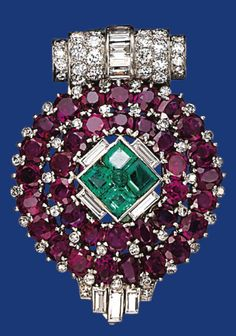 AN ART DECO RUBY, EMERALD, ENAMEL AND DIAMOND CLIP BROOCH  The circular bombé panel set with two rows of oval-shaped rubies centering upon square-cut emeralds with green enamel bead center, to the pavé-set diamond scroll top and baguette-cut diamond detail at the bottom, 1930s, 4.6 cm, with French assay marks for platinum and gold