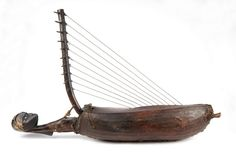 Harpe à dix cordes en boyau. Caisse de résonance en bois foncé recouverte d'une peau servant de table de résonance comportant une ouïe circulaire, et fixée au dos par un laçage de cuir. La caisse se prolonge, derrière le manche, d'une sculpture représentant une tête humaine aux traits rehaussés de clous de cuivre et de lignes gravées et blanchie. Le manche, légèrement arqué, est emboîté et fixé dans la caisse par des cordelettes -  Ngombe - République centrafricaine