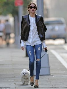 Out for a trot: Olivia was looking breezy and chic in tight ripped jeans as she took her fluffy white dog Mr. Butler out for a walk in New Y...