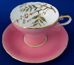 This is a vintage Aynsley China, England bone china cup and saucer in a pretty pink on white with a an interior pattern of a brown transferware tree branch with berries that has been hand colored and then accented with red enamel with gold trim The pattern is number 1569/9 and the teacup was made in the 1950s.