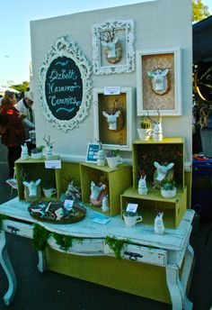 Great small booth display idea. I love the frames, ornate table and boxes.