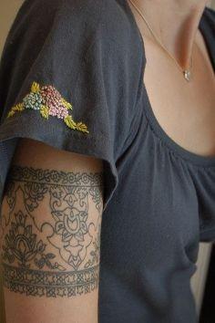 un tatouage dentelle entourant le bras