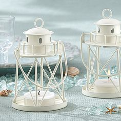 Lighthouse Tealight Candle Holders are made of a cream-hued sturdy metal with detailed windows and railing around the lantern top.