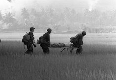 U.S. troops carry the body of a fellow soldier across a rice paddy for helicopter evacuation near Bong Son in early February 1966. The soldier, a member of the 1st Air Cavalry Division, was killed during Operation Masher on South Vietnam's central coast.