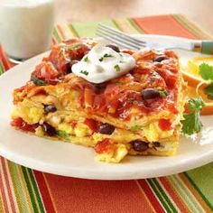 Scrambled eggs, black beans, cilantro, garlic and green onions are layered with corn tortillas for a Southwestern brunch bake.